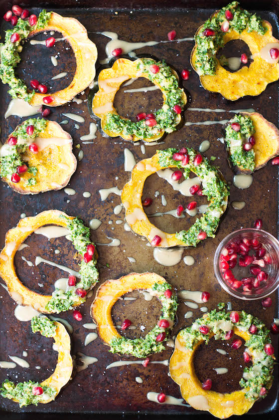 Overhead shot of rings of squash with kale and pomegranate seeds