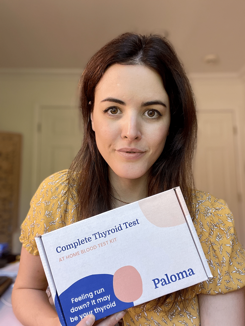 woman holding a Paloma thyroid test kit