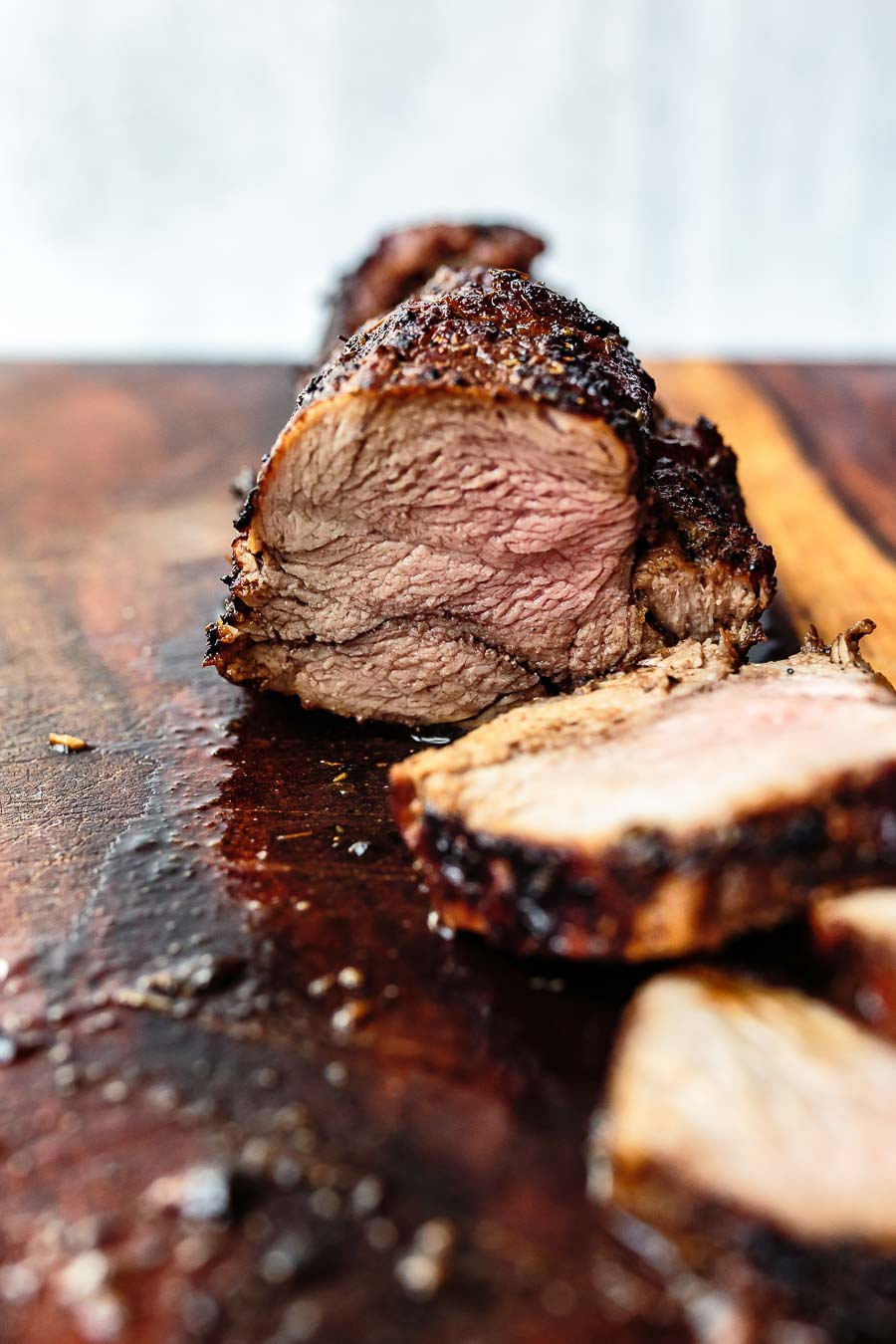 sliced balsamic pork tenderloin on cutting board