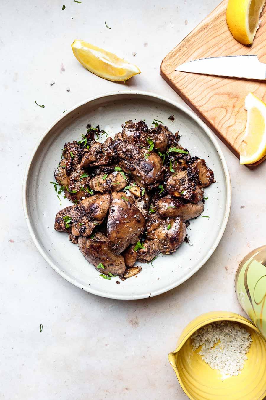lemon garlic chicken liver with fresh parsley and lemon wedges