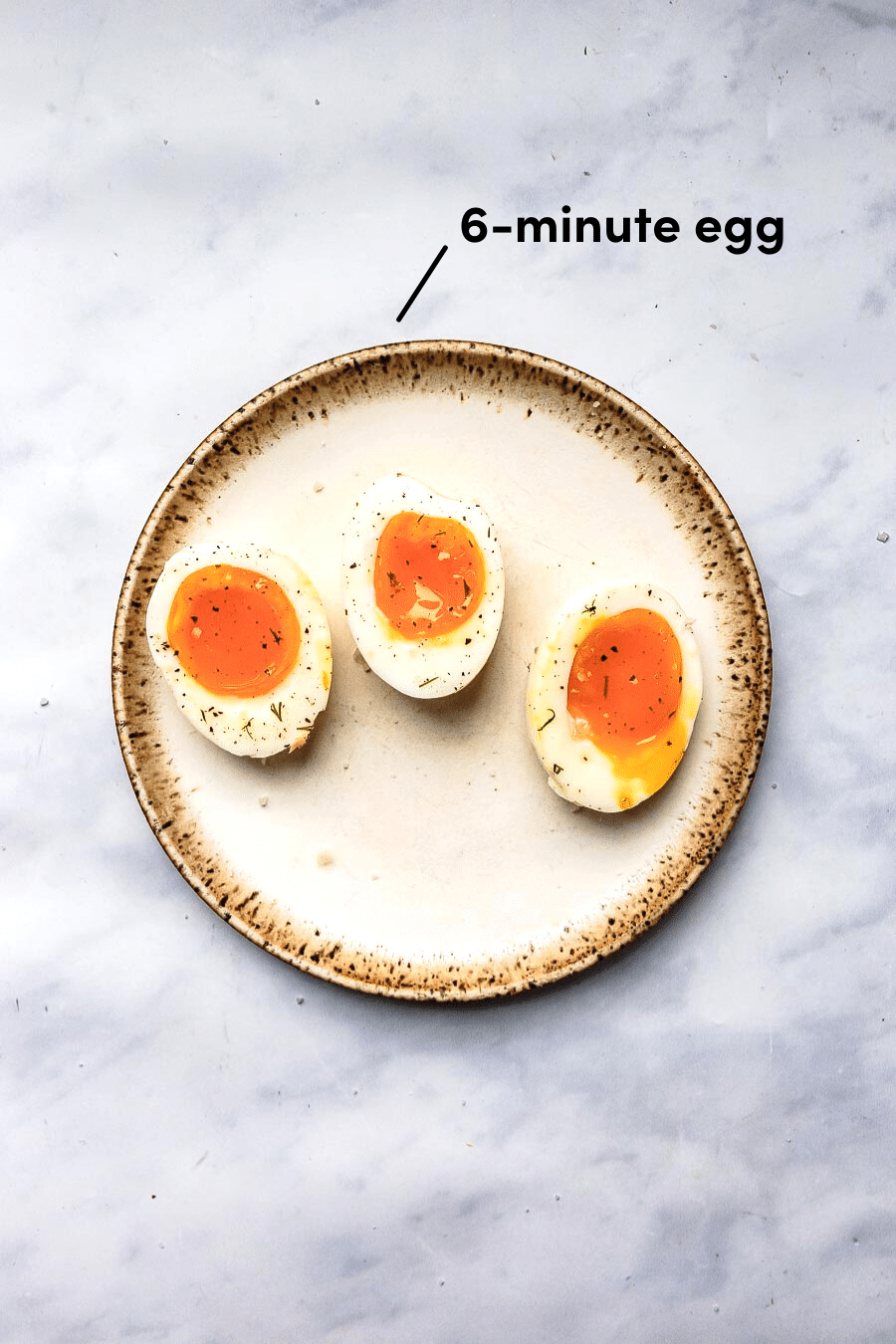 three jammy boiled eggs halved and resting on a stoneware place topped with salt and pepper and 6-minute cook time indicator