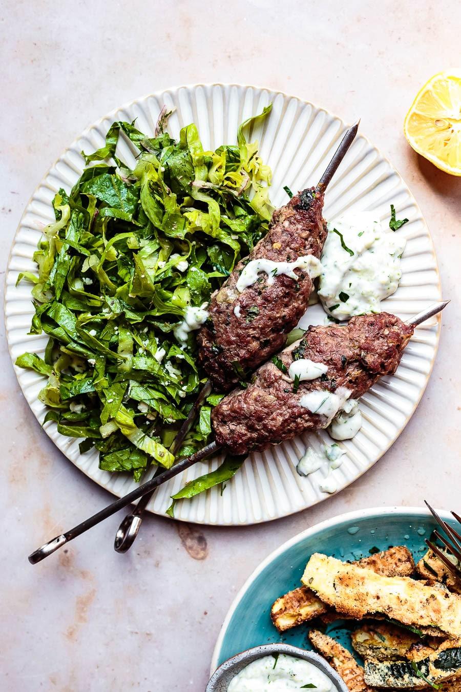 baked greek kofta kebabs with green salad and tzatziki on a plate