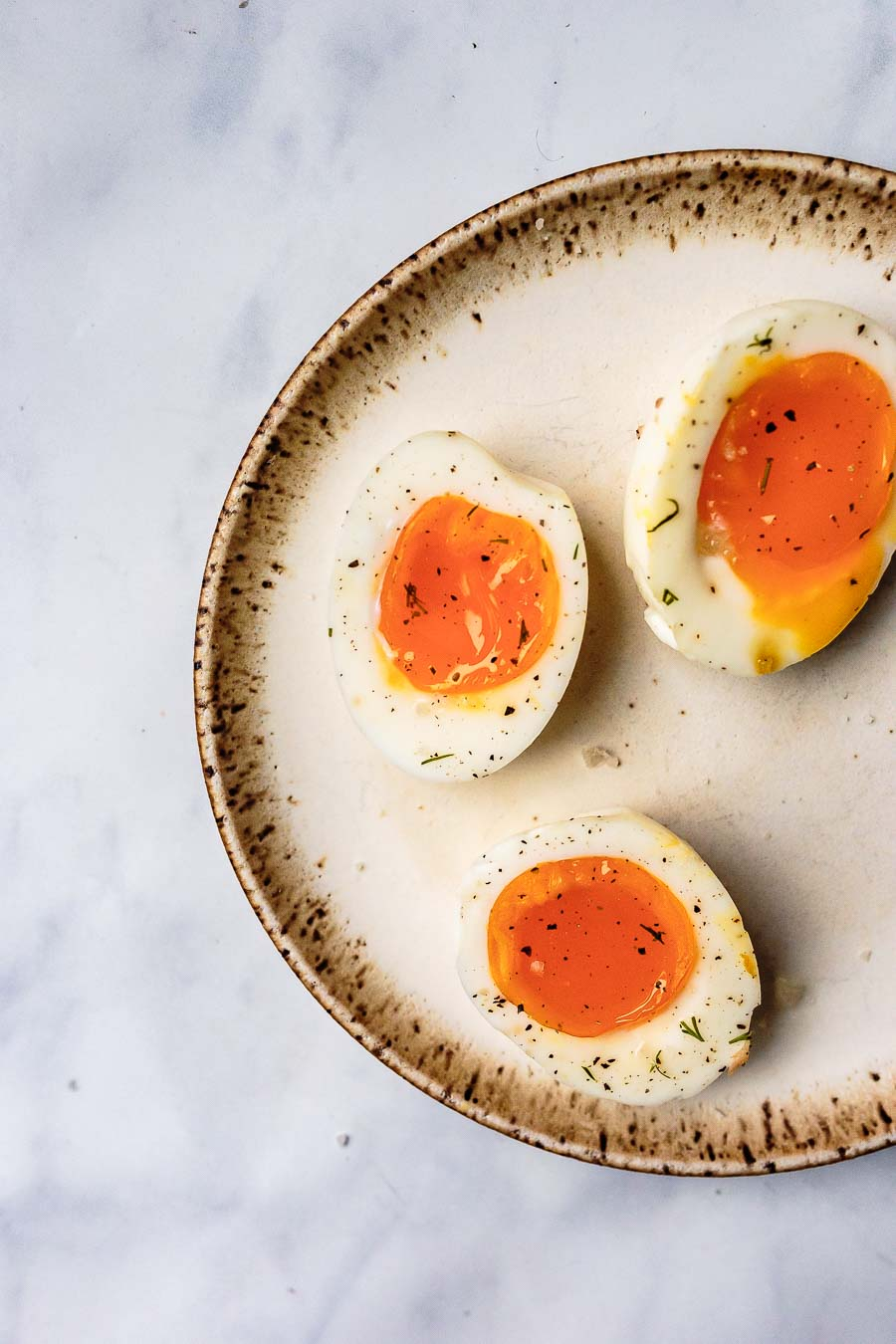 three jammy boiled eggs halved and resting on a stoneware place topped with salt and pepper