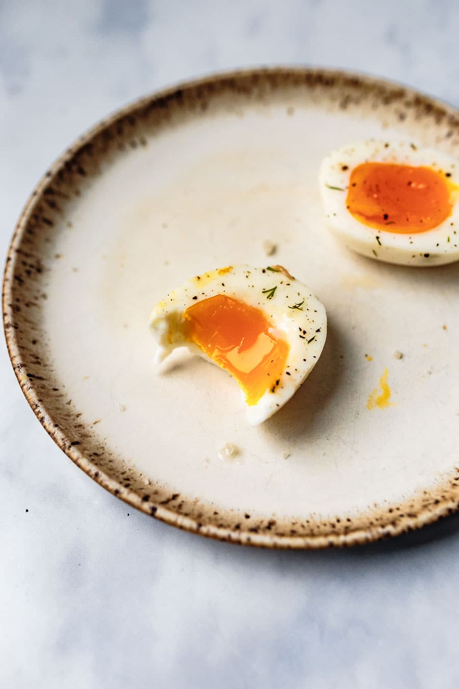 three jammy boiled eggs halved and resting on a stoneware place topped with salt and pepper and a bite taken out of one of them