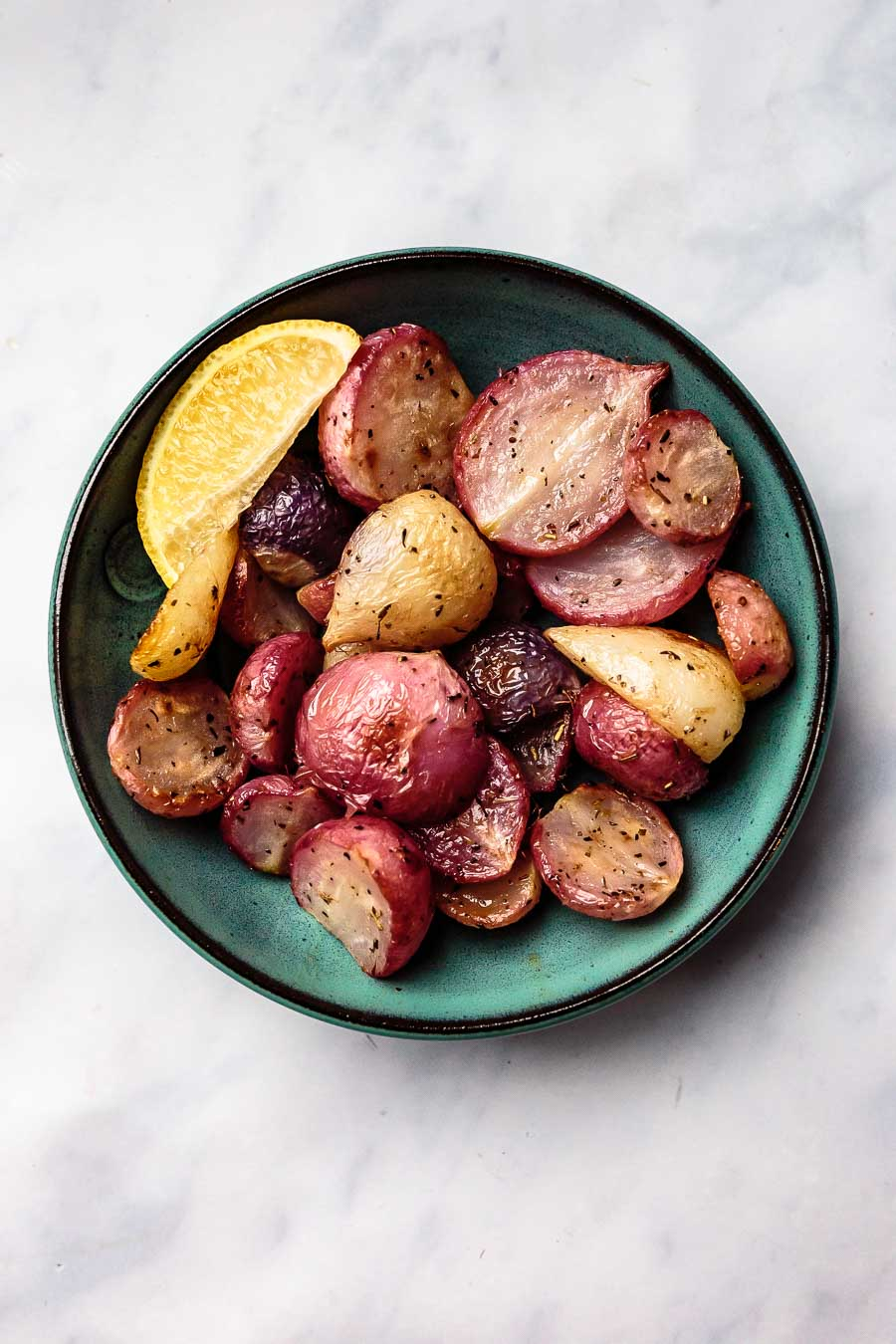 a teal bowl full of roasted radishes with a lemon wedge